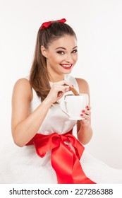 Portrait of young attractive woman with pinned-up ponytail with a red bow holding a mug and dipping  a cookie. Wearing a white christmas dress.