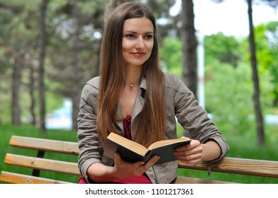 Portrait of a young attractive woman in a red dress sitting on a bench in a city park and reading a book