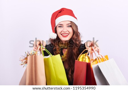 38a5d22ce6755 Portrait of a young attractive woman in red Santa Claus hat holding  colorful shopping bags in