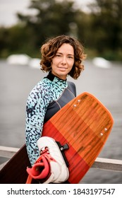 Portrait of young attractive woman with short curly hair in wetsuit with bright wakeboarding board in her hand.