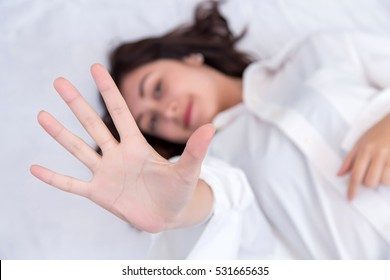 Portrait of a young attractive woman showing stop sign with hand on her bedroom