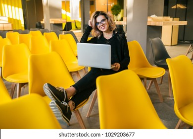portrait of young attractive woman sitting in lecture hall, working on laptop, wearing glasses, classroom, many yellow chairs, student learning, education online, freelancer, relaxed, hipster style