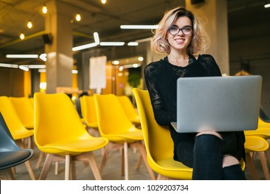 portrait of young attractive woman sitting in lecture hall, working on laptop, wearing glasses, classroom with many yellow chairs, student learning, education online, freelancer, smiling, stylish
