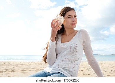 Portrait of a young attractive woman sitting on a white sand beach on vacation, holding a sea shell to her ear and listening to the ocean waves while relaxing and smiling. Outdoors holiday lifestyle.