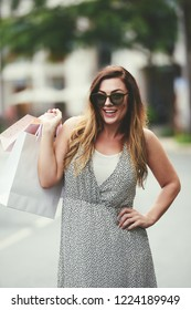 Portrait of young attractive woman in sunglases holding shopping bags