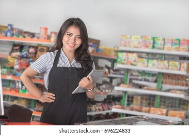 portrait of young attractive woman with tablet pc in a store