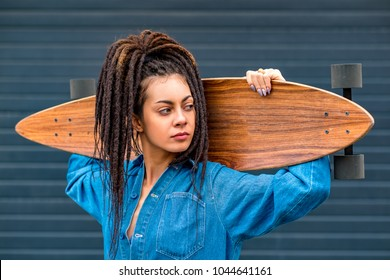 Portrait of young attractive woman or teenage girl in blue denim romper shirt with dreadlocks holding wooden longboard skateboard on her shoulders. Urban scene, city life. Hipster cute lady.