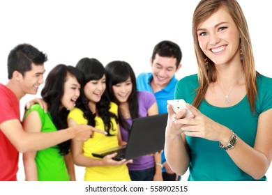 portrait of young attractive woman using mobile phone while her friend at the background using laptop together