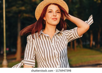 portrait of young attractive woman wearing striped dress and straw hat