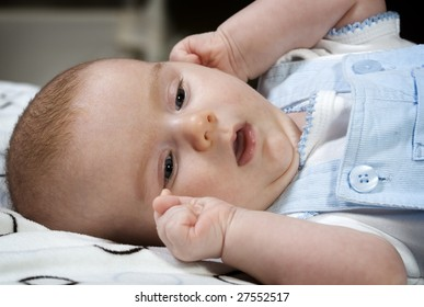 Portrait of young baby boy laying on blanket