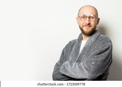 Portrait of a young bald man with a beard in a dressing gown and glasses with arms crossed on his chest on an isolated light background. Emotional face