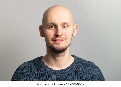 portrait of a young bald man in a knitted sweater on a gray background