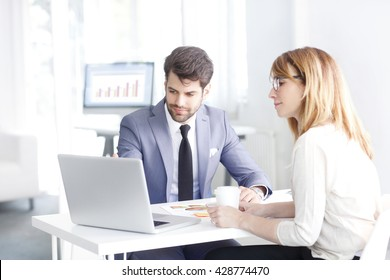 Portrait of young bank officer consulting with businesswoman while sitting at office in front of laptop.