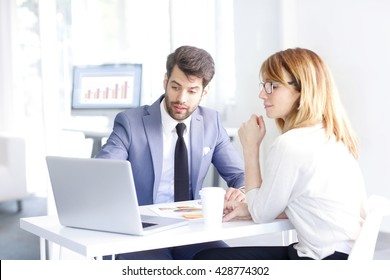 Portrait of young banking advisor sitting in front of laptop and helping a client with her banking accounts.