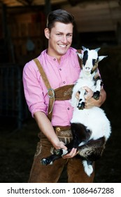 portrait of young bavarian man holding a goat