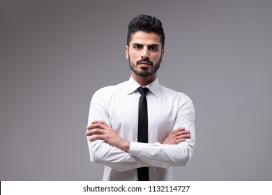 Portrait of young bearded bossy man wearing white shirt with necktie