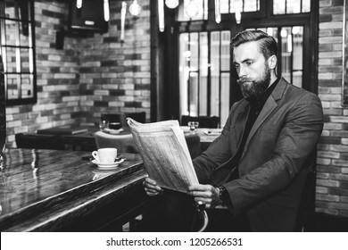 Portrait of a young bearded businessman sitting at the bar, reading newspapers and drinking coffee.