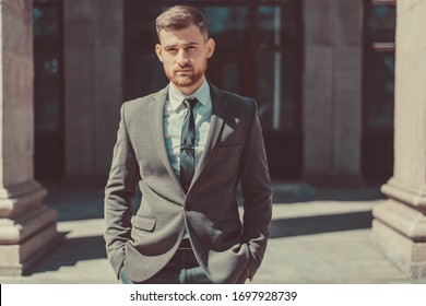 Portrait of a young bearded guy of twenty-five years old, in a business suit, against the background of an office building. Posing looking at the camera. Outdoors
