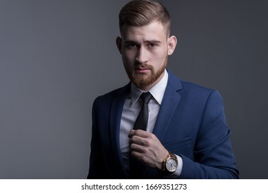portrait of a young bearded handsome guy in a business suit, looking at the camera, demonstrating a wristwatch, with a leather strap. Advertising men's watches. On a gray background.