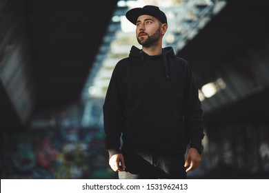Portrait of a young bearded man with a black hat ain black hoodie in the city