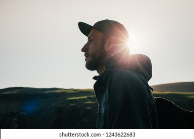 Portrait of young bearded man in five panel cap walk at sunset, look ahead towards horizon, thoughtful and deep stare, motivational and inspiring millennial explores world around