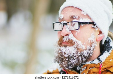 Portrait of a young bearded man frozen in a Blizzard in the woods. Face, beard , mustache and glasses covered with frost. Face covered with snow.