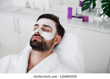 Portrait of a young bearded man having his eyes closed while being in the white bathrobe and having white mask on his face