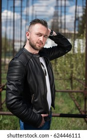 portrait of  young bearded  man in leather jacket leaned on wall
