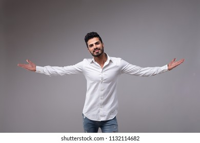 Portrait of young bearded man with outstretched arms wearing white shirt