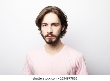Portrait of young bearded man posing over white background, casual style