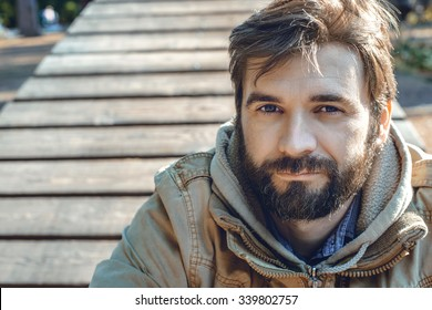 Portrait of young bearded man. Retro film filtered.Portrait of a young man in a park.