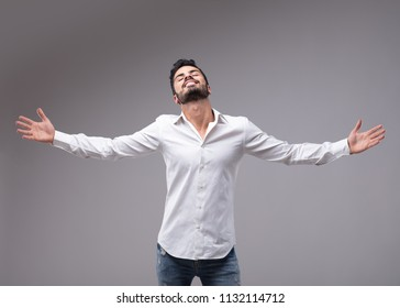 Portrait of young bearded man wearing white shirt showing relieved gesture with outstretched arms