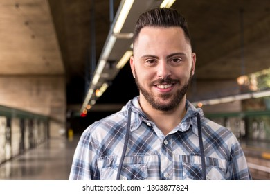 Portrait of Young bearded man wearing plaid shirt waiting for train at subway station. Concept of commute, transport service, mobility.