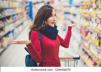 Portrait of young beatiful brunette woman looking surprised at the shelf in the supermarket
