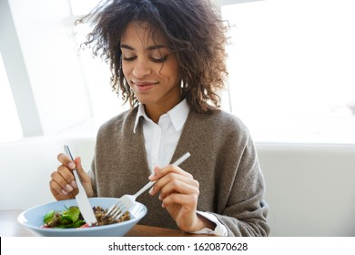 Portrait of young beautiful african american woman eating salad while having lunch in cafe