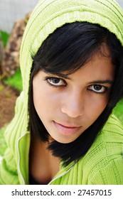 Portrait of young beautiful african american teen girl in green hood.