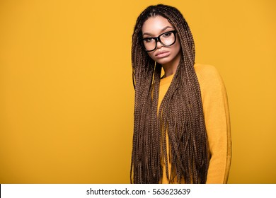 Portrait of young beautiful african american teenager girl with long braids hairstyle and fashionable eyeglasses. Yellow background.
