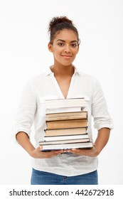 Portrait of young beautiful african girl in white blouse looking at camera, smiling with books over white background.