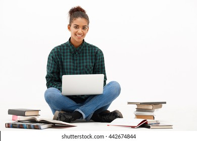 Portrait of young beautiful african girl with laptop and books smiling, looking at camera over white background. Copy space.