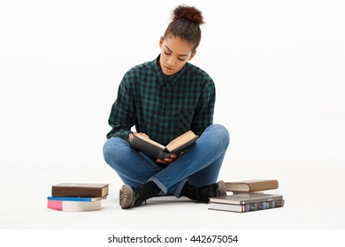Portrait of  young beautiful african girl in green blouse and jeans sitting on floor, reading book over white background. Copy space.