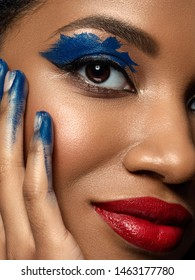 Portrait of young beautiful african woman with fashion make up. Red lips, blue eyeshades and black eyeliner. Studio shot. Extreme closeup, partial face view