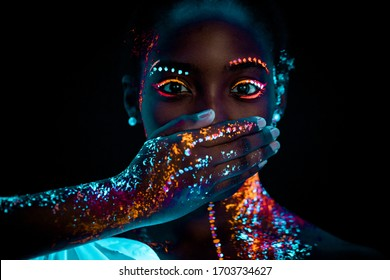 portrait of young beautiful african woman with fluorescent prints on face and closed mouth. fluorescent prints glowing on ultra violet rays, keep silence gesture