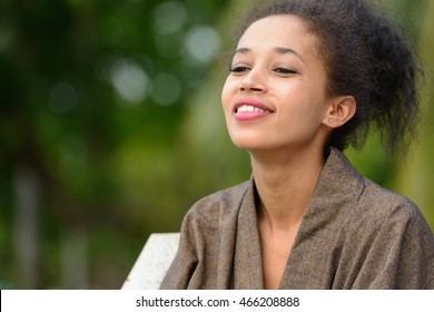 Portrait of young beautiful African woman outdoors in park