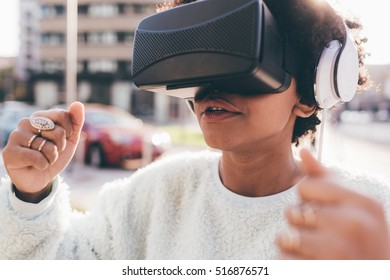 Portrait of young beautiful afro woman using 3d viewer outdoor in the city with head phones in back light - technology, video game, futuristic concept
