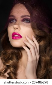 Portrait of young beautiful aristocratic woman with bright pink lips wearing purple veil and touching her face