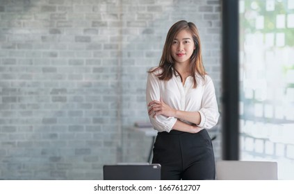 Portrait of young beautiful asian businesswoman smiling and standing with arms crossed in modern office, looking at camera, copy space.
