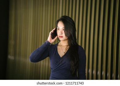 Portrait of a young and beautiful Asian Chinese woman in a classy and elegant blue dress against a modern gold feature wall. She is talking on her phone and is frowning, looking concerned and worried.