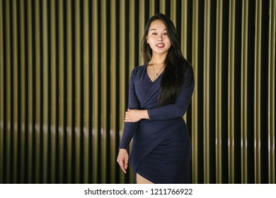 Portrait of a young and beautiful Asian Chinese woman in a classy and elegant blue dress against a modern gold feature wall. She is smiling enigmatically and posing for her photo.