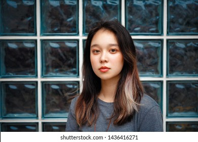 A portrait of a young and beautiful Asian girl. chinese teen girl against a wall of glass. young asian woman model. in gray shirt. trendy chinese teenager