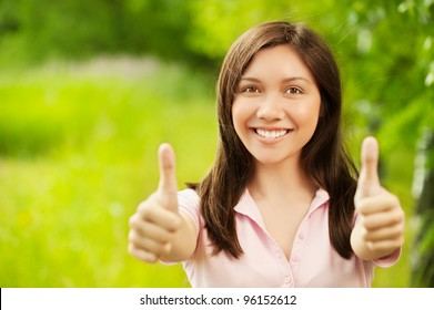 Portrait of young beautiful asian girl showing thumbs up at summer green park